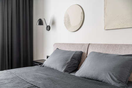 Trendy modern bedroom with white wall with relief pictures. There is a double bed with gray linens and pillows, hanging lamp, black nightstand, dark curtain. Horizontal. Zdjęcie Seryjne