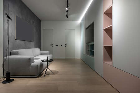 Stylish modern interior with different walls and a parquet on the floor. There is a gray sofa with a laptop, black round stand, luminous lamps, doors, multicolored lockers with shelves, TV.