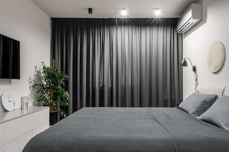 Luminous modern bedroom with white walls with a relief picture. There is a double bed with gray linens and pillows, black hanging lamp, dark curtains, green plant in the pot, TV, light stand, lamps.