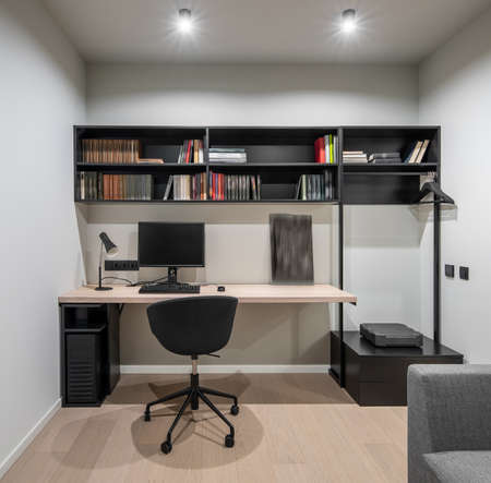 Wonderful luminous modern room with white walls and a parquet. There is a wooden table with a lamps and a computer, black shelves with books, chair, drawers, rack with hangers, gray sofa. Horizontal.