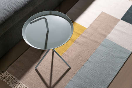 Fancy metal round light stand on the multicolored carpet on the parquet floor in the luminous interior. There is a gray sofa near it. Closeup. Horizontal.