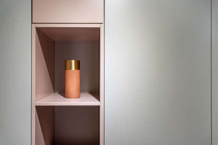 Pink shelves with a orange vase between gray lockers in the luminous interior. Closeup. Horizontal. Zdjęcie Seryjne