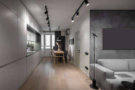 Contemporary kitchen with light walls and a parquet. There are gray lockers, sink, stove, oven, wooden table with vase and chairs, window with curtain, luminous lamps, door, sofa with a laptop, stand.