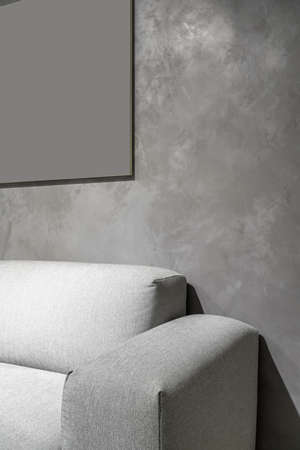 Gray sofa on the background of the textured wall in the luminous interior. Closeup. Vertical.