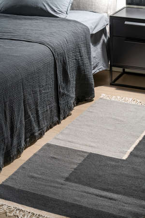 Illuminated bedroom with a multicolored carpet on the parquet floor. There is a bed with gray linens with a coverlet and a pillow, black nightstand. Closeup. Vertical. Zdjęcie Seryjne