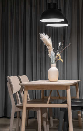 Wooden table with light and dark chairs on the curtains background indoors. There is a beige vase with dried plants on it and luminous black lamps over it. Closeup. Vertical. Zdjęcie Seryjne
