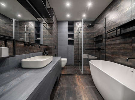 Great illuminated modern bathroom with textured bronze tiled walls and floor. There is a gray stand with drawers and a white sink, wide mirror, glass shower cabin, bath, toilet, shelves, lockers.