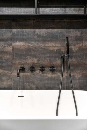 Stylish illuminated modern bathroom with textured bronze tiled walls. There is a white bath with a dark matte faucet and shower, black shelves. Closeup. Vertical.