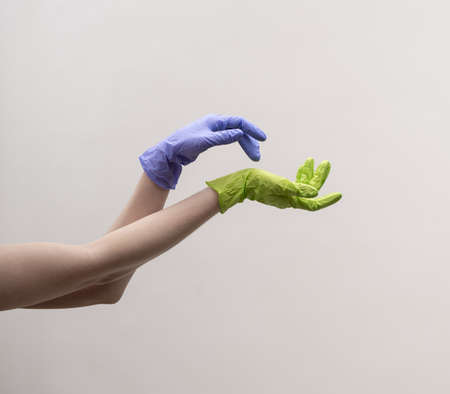 Aesthetic female hands in multi-colored silicone gloves. Zdjęcie Seryjne