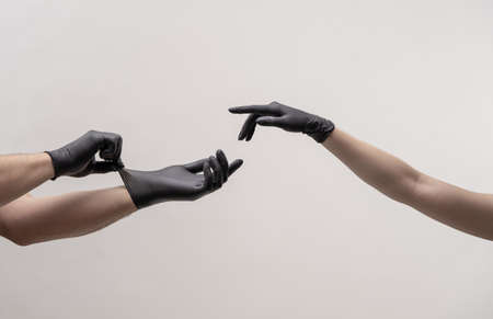 Male and female hand in black gloves stretch to touch each other. The male hand adjusts the glove with the second hand. Zdjęcie Seryjne