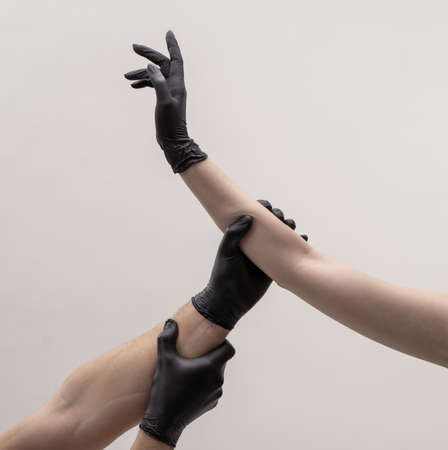 Hands in black silicone gloves stretches to each other to touch Zdjęcie Seryjne