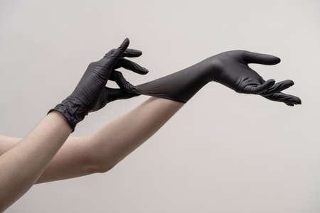 Aesthetic female hands in black silicone gloves on a light background. One hand adjusts the glove on the other hand. Zdjęcie Seryjne