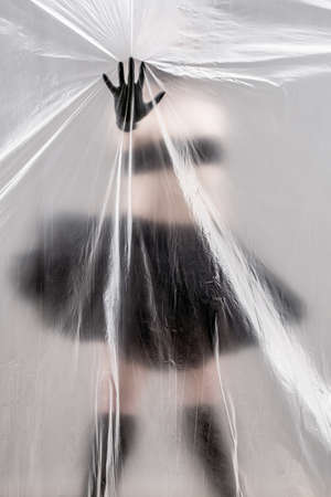 Ballerina in a black ballet skirt stands behind a curtain of plastic film. Girl in a black mask on her face and black gloves on her hands. The dancer touches the plastic with her palm, the film covers her face. Symbol of self-isolation in the conditions of COVID19 virus quarantine.