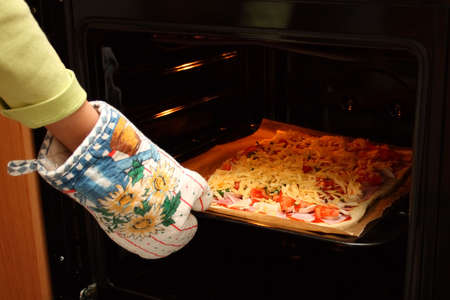 Home-made pizza with cheese, tomatos and mushrooms. Placing in the oven photo