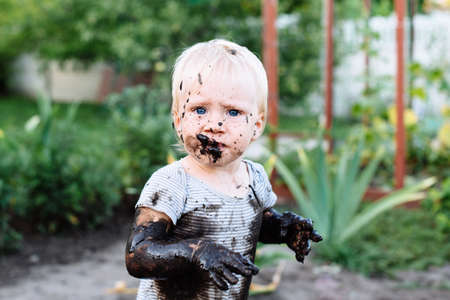 child with blue eyes playing in the mud in the summer on the street