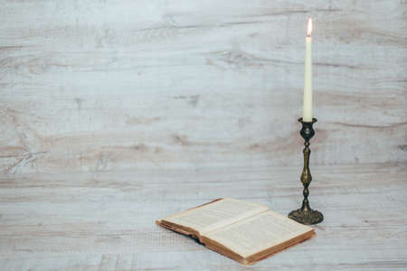 antique candlestick with a burning candle on a wooden background