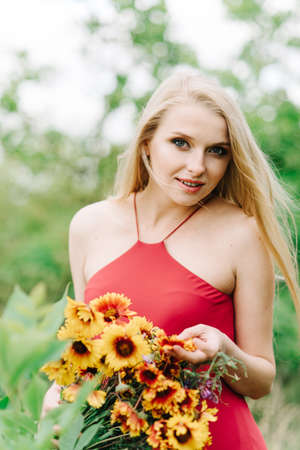 young girl with white hair on nature on a green background with a bouquet of yellow flowers without photoshop Stock Photo