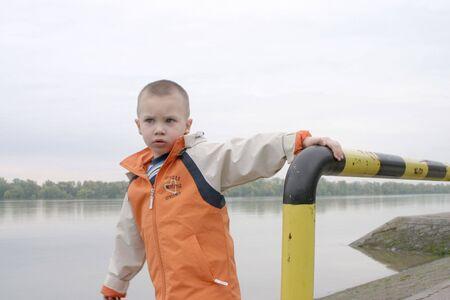 boy in orange jacket on riverside photo