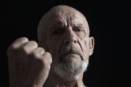 servile: portrait of senior with fist