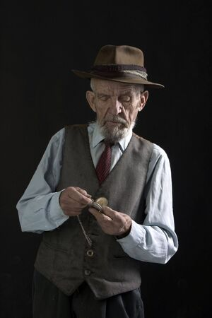 servile: old man is looking the watch Stock Photo