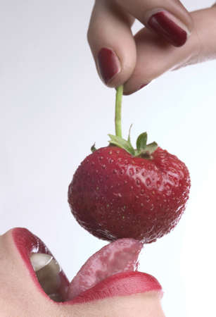 red lips is eating red strawberry Stock Photo