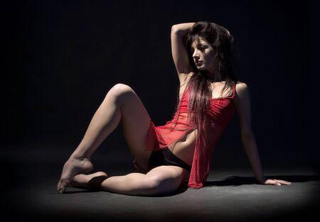 female dancer in red dresssitting on the floor
