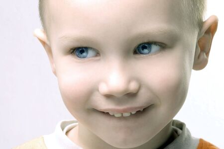 face shoot of blond happy boy with big smile photo