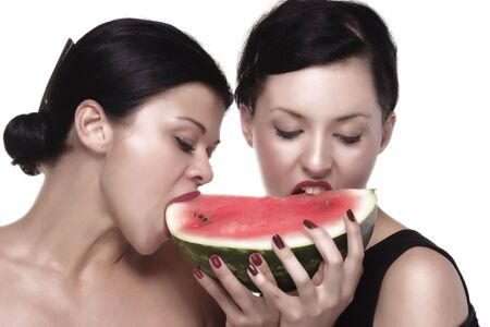 girls are eating melon Stock Photo