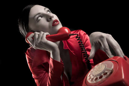 lady in red is talking  by old red phone Stock Photo - 897259
