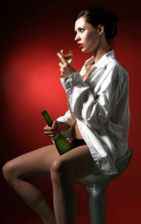 a woman is sitting in white men shirt with bottlerof white wine