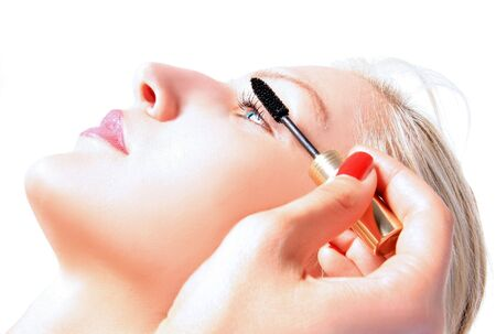eye lashes: the girl is putting a mascara on eye lashes
