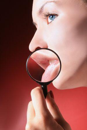 cremas faciales: Retrato de una mujer con lupa centr�ndose en sus labios  Foto de archivo