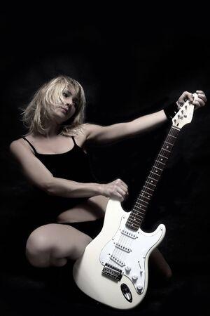 ブロンドの女の子が白い電機ギターを保持しています。