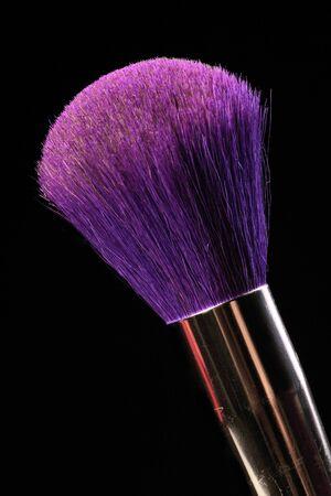 beautycare: purple cosmetic brush on the black background