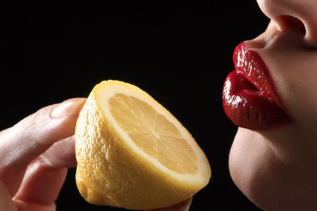 red woman lips with hand holding lemon photo
