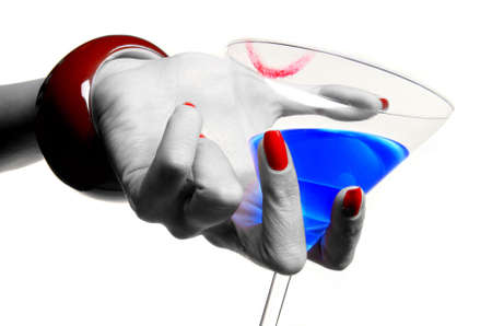 a female hand with red nails is holding a coctail photo