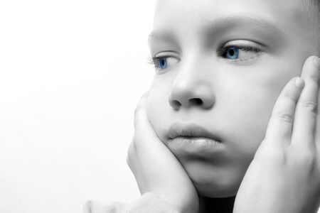 a blond boy with blue eyes looking sad Stock Photo