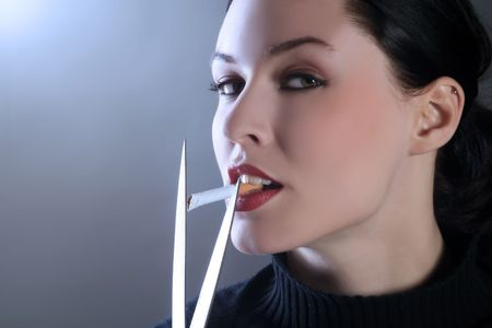 a female is cutting cigarette in her mouth Stock Photo