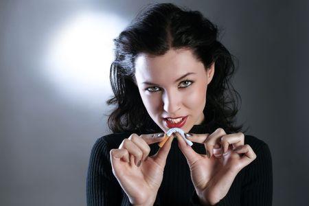 persona fumando: una muchacha de la belleza est� rompiendo el cigarrillo