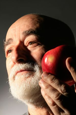 losing knowledge: a senior gentleman with apple on gray background Stock Photo