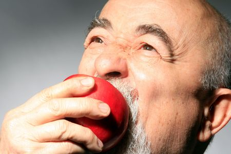 losing knowledge: a senior gentleman is bitting red apple Stock Photo