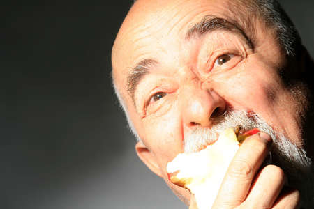 losing knowledge: face shot og a senior gentleman with apple in mouth
