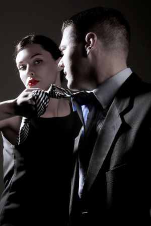 a business lady is pulling mans tie on the black Stock Photo