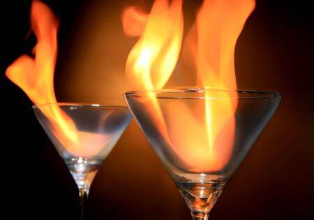 copa de martini: dos c�cteles con fuego en el fondo blanco Foto de archivo