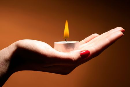 a burning candle in female hand on orange