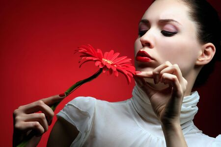 a beauty brunette with red flower looking at it Stock Photo - 3055648