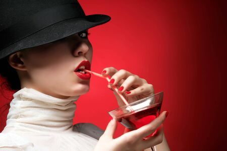 a glamor lady with hat is drinking cocktail Stock Photo