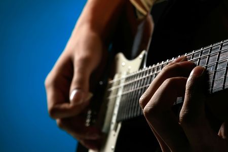 a man is playing an electric guitar on blue Stock Photo