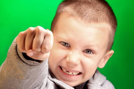 a punching boy on the green background photo
