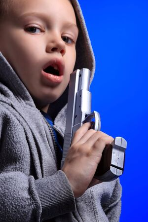 a blond boy on the blue with gun